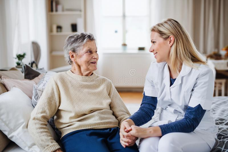 A health visitor talking to a sick senior woman sitting on bed at home. royalty free stock images