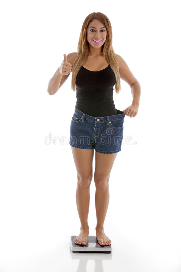 Health: Weight Loss. Pretty fit woman dressed casually, Looking at camera , giving thumbs up and smiling at her weight loss. Shot on a white background royalty free stock images