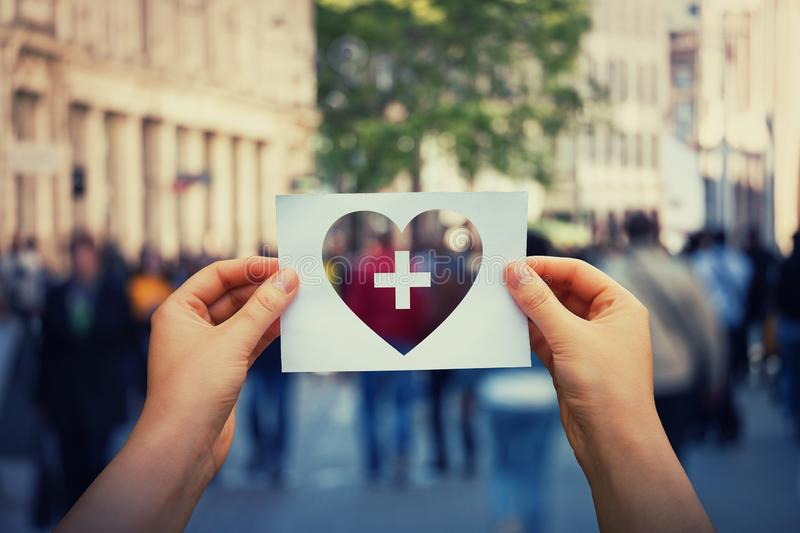 Health and wellbeing problem. Health and wellbeing global issue as human hands holding a paper sheet with heart and cross icon over a crowded street background stock photography