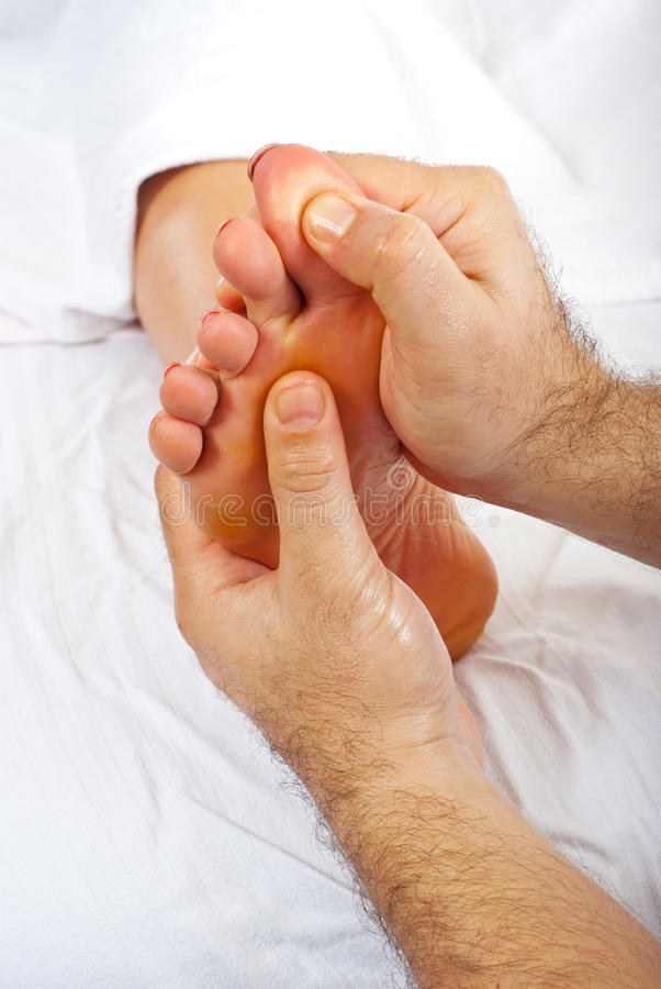 Health worker give reflexology massage stock image
