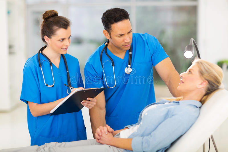 Health workers patient. Caring health workers talking to middle aged patient before checkup royalty free stock photo