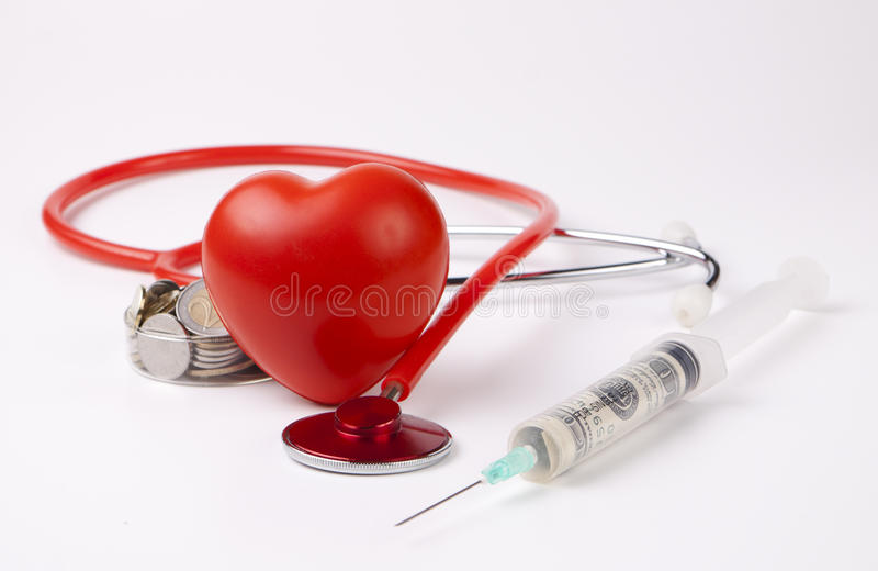 Healthcare. Cost money coins and bills with a red stethoscope and big red heart royalty free stock photography