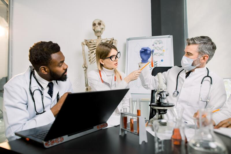 Healthcare and biotechnology concept. Multiethnic young scientists work in laboratory. Man in mask shows test tube with. New substance or blood to African man stock photo