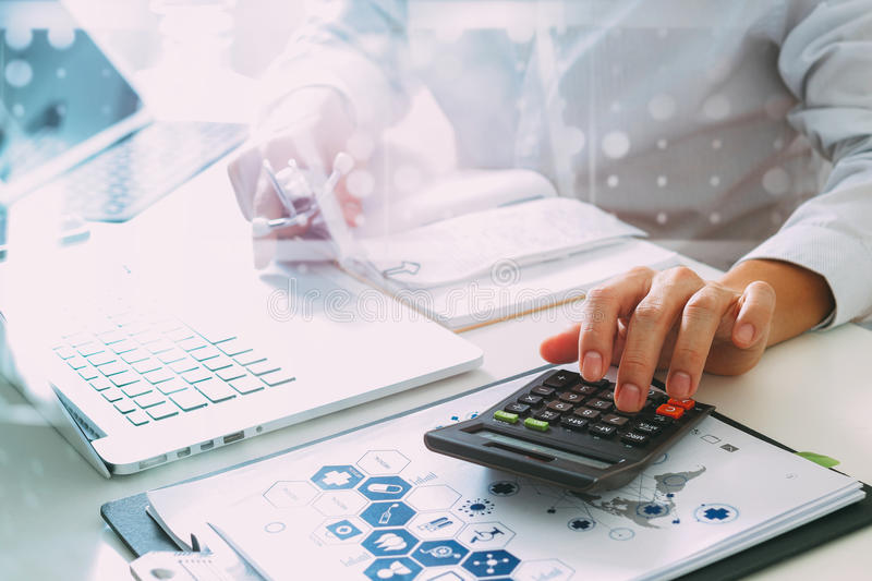 Healthcare costs and fees concept.Hand of smart doctor used a ca. Lculator for medical costs in modern hospital stock photo