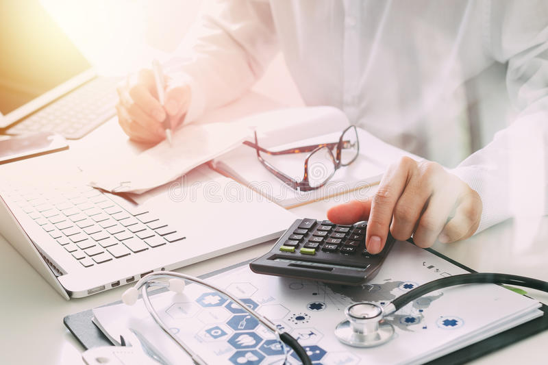 Healthcare costs and fees concept.Hand of smart doctor used a ca royalty free stock photo