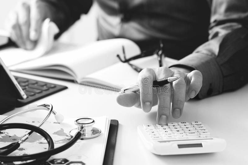 Healthcare costs and fees concept.Hand of smart doctor used a ca. Lculator for medical costs in modern hospital,black and white stock photography