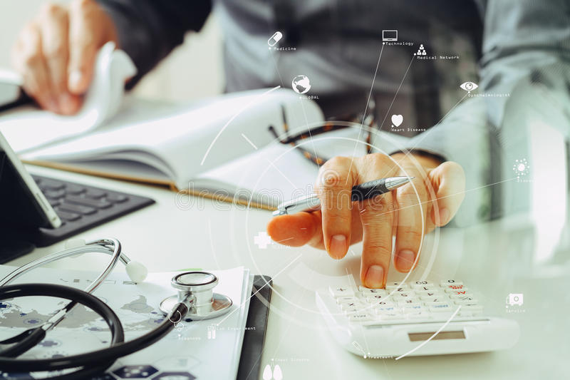 Healthcare costs and fees concept.Hand of smart doctor used a ca. Lculator for medical costs in modern hospital with VR icon diagram royalty free stock photos