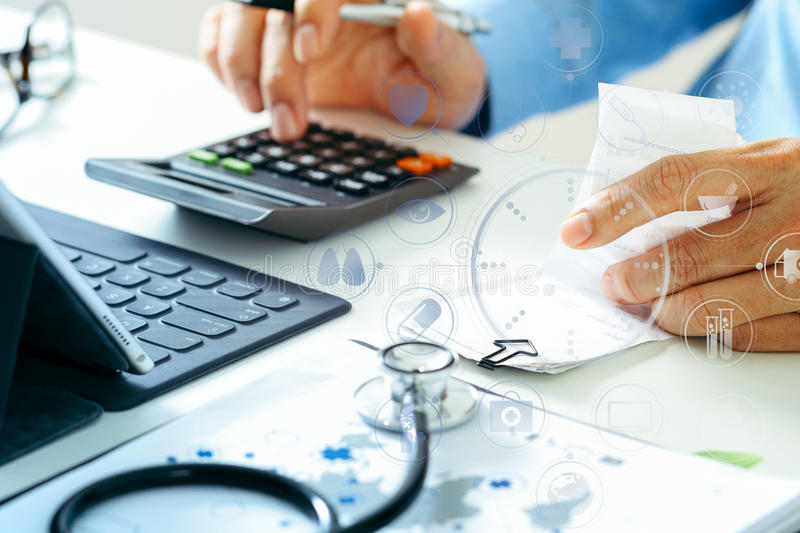 Healthcare costs and fees concept.Hand of smart doctor used a ca. Lculator for medical costs in modern hospital with VR icon diagram royalty free stock images