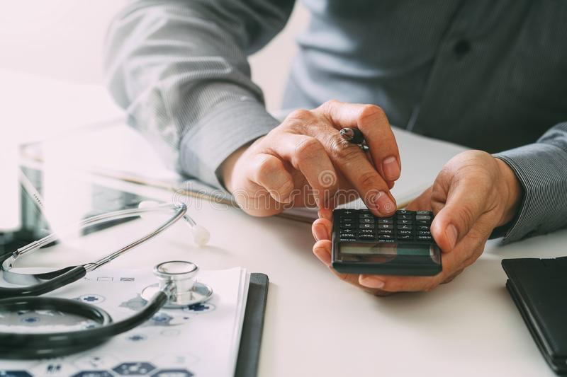 Healthcare costs and fees concept.Hand of smart doctor used a ca. Lculator for medical costs in modern hospital royalty free stock photo