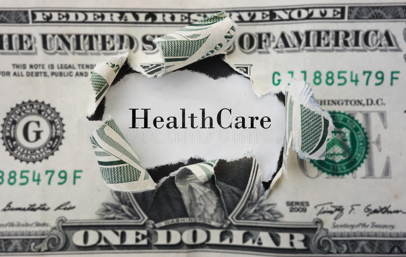 Healthcare costs. Hole torn in a dollar bill with Healthcare text stock photo