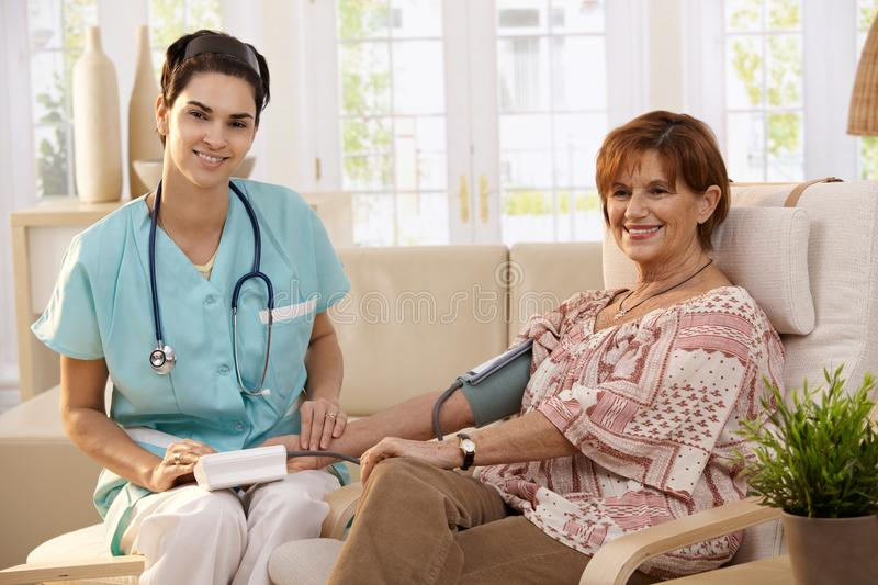 Healthcare at home. Female doctor measuring blood pressure of senior women at home. Looking at camera, smiling royalty free stock photo