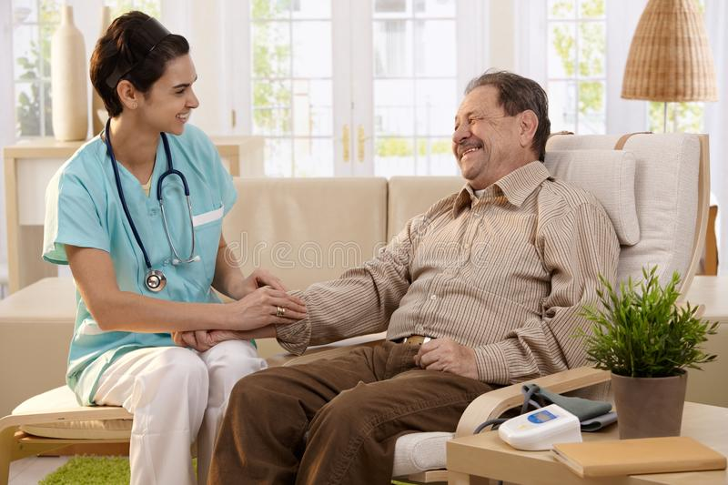 Healthcare at home. Nurse measuring blood pressure of senior men at home. Smiling to each other royalty free stock image