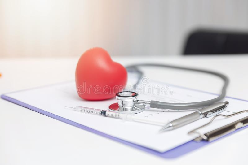 Healthcare and medical concept, Closeup stethoscope ,injection needle and heart on medical treatment chart.  royalty free stock images
