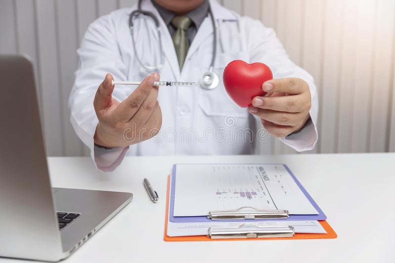 Healthcare and medical concept,Doctor holding injection needle and heart ball.  royalty free stock image