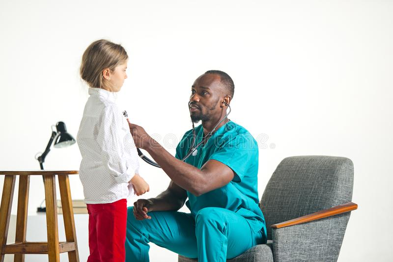 Healthcare and medical concept - doctor with stethoscope listening to child chest in hospital stock image
