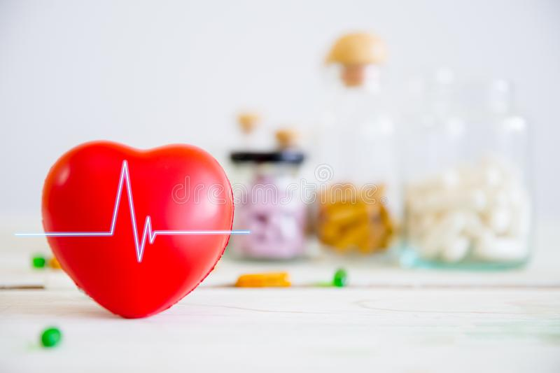 Healthcare and medical concept. Red heart on wooden table with set of medicine bottles and medicine pills background. royalty free stock images