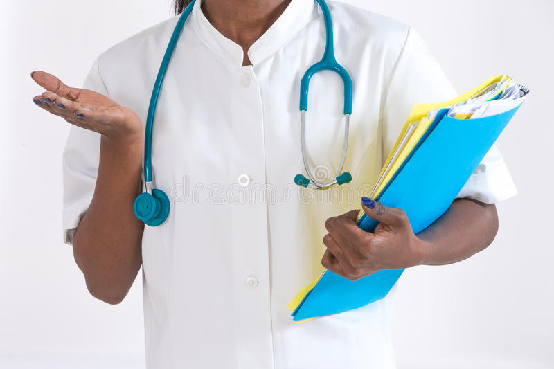 Healthcare and medical concept - smiling african female doctor in hospital stock photography