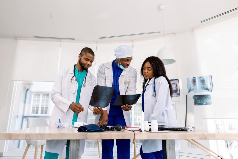 Healthcare, medical: Group of three young African doctors, two men and woman, discuss and looking x-ray in a clinic or royalty free stock photo