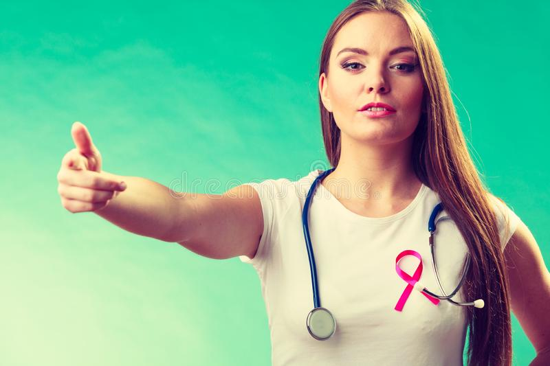 Woman pink ribbon on chest making welcome gesture royalty free stock photography