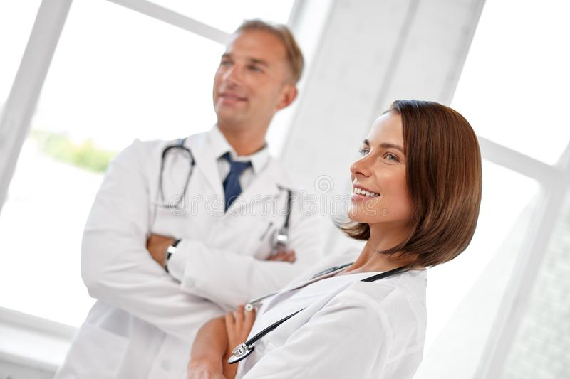 Smiling doctors in white coats at hospital royalty free stock photo