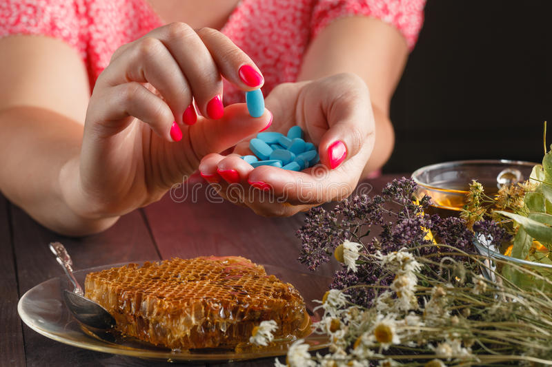 Healthcare and medicine: Young woman has control over pills. With relax herbs royalty free stock photos