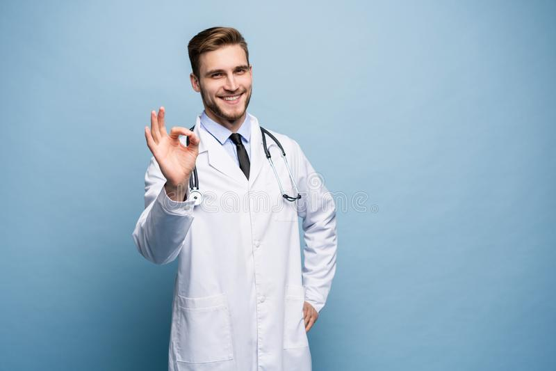 Healthcare, profession, gesture, people and medicine concept - smiling male doctor in white coat showing ok hand sign. royalty free stock image