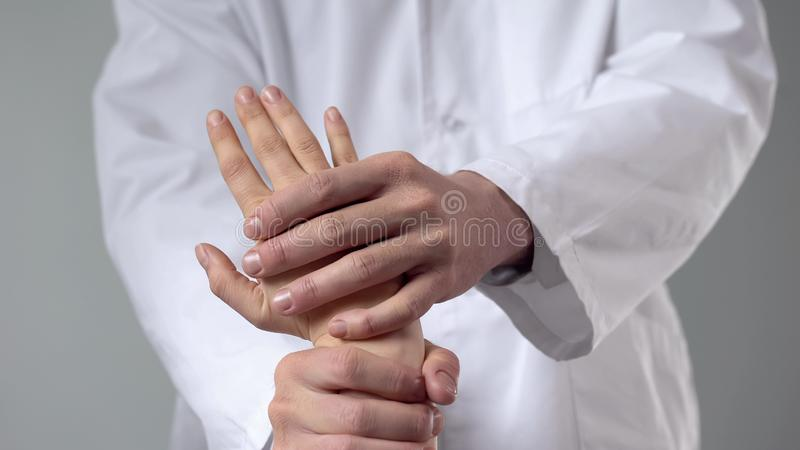Healthcare specialist examining injured wrist, alternative medicine treatment stock image
