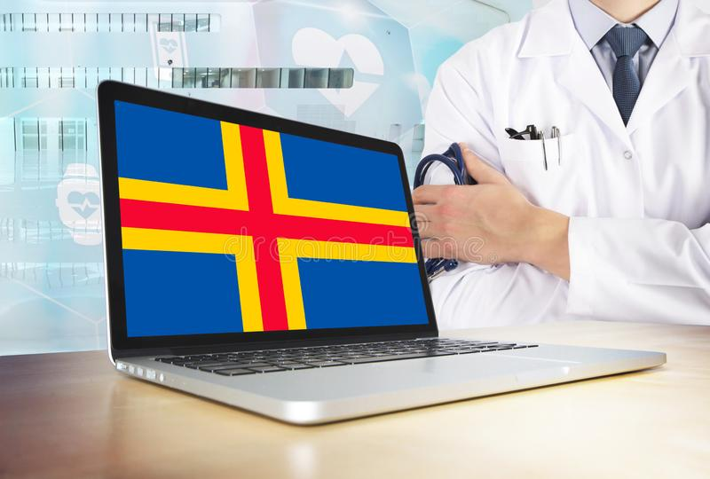 Healthcare system in tech theme. Aland Islands flag on computer screen. Doctor standing with stethoscope in hospital. Cryptocurrency and Blockchain concept stock photo