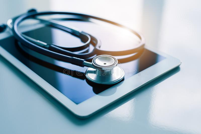 Healthcare concept - tablet and stethoscope on white table royalty free stock image