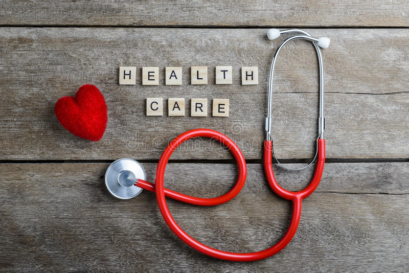 Healthcare text word made with wood blocks and Red Heart,stethoscope on wooden table royalty free stock photo