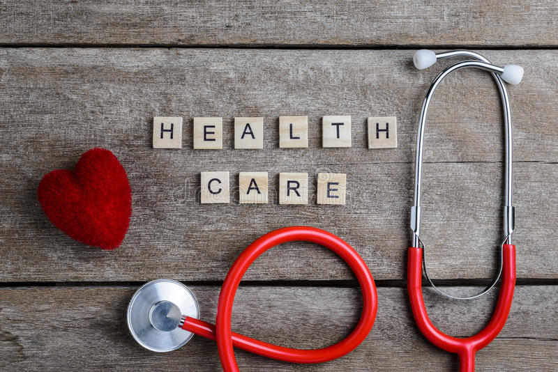 Healthcare text word made with wood blocks and Red Heart,stethoscope on wooden table stock image