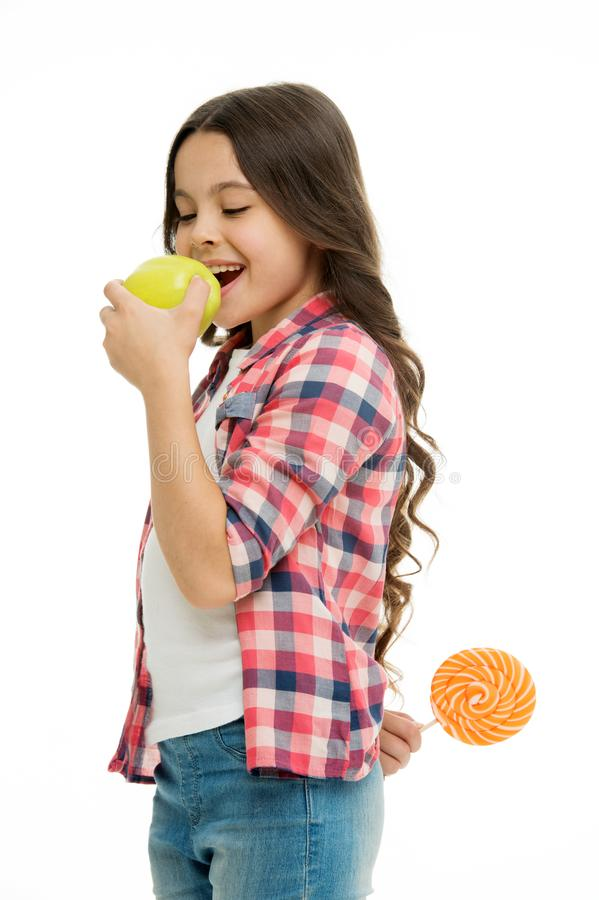Healthcare tricks. Kid girl cunning eats apple while holds lollipop behind back. Whom she tries to trick. Girl pretend royalty free stock photo