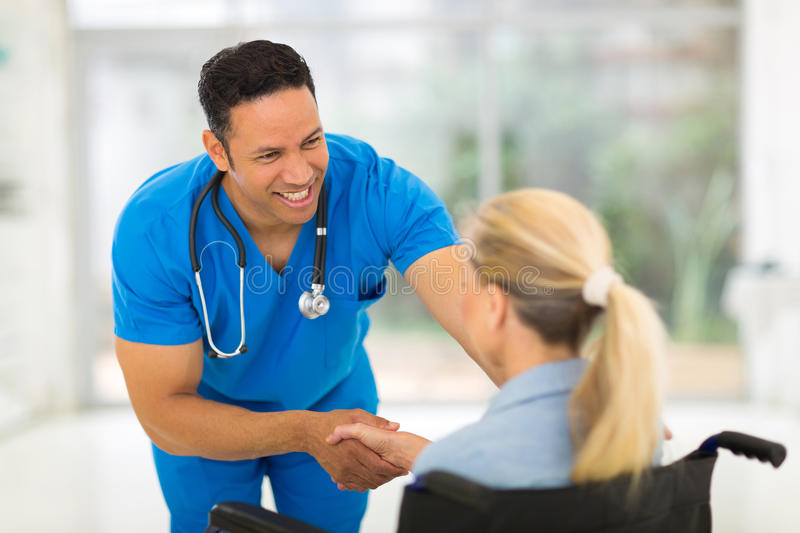 Healthcare worker handicapped. Friendly healthcare worker handshaking handicapped woman royalty free stock photography