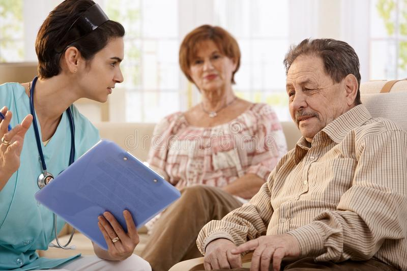 Healthcare worker at home of pensioners. Nurse talking with elderly people showing test results during routine examination at home royalty free stock images