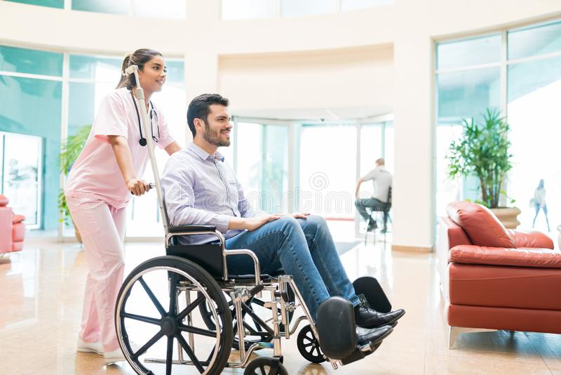Healthcare Worker Leaving Mid Adult Male Patient In Hospital stock photo