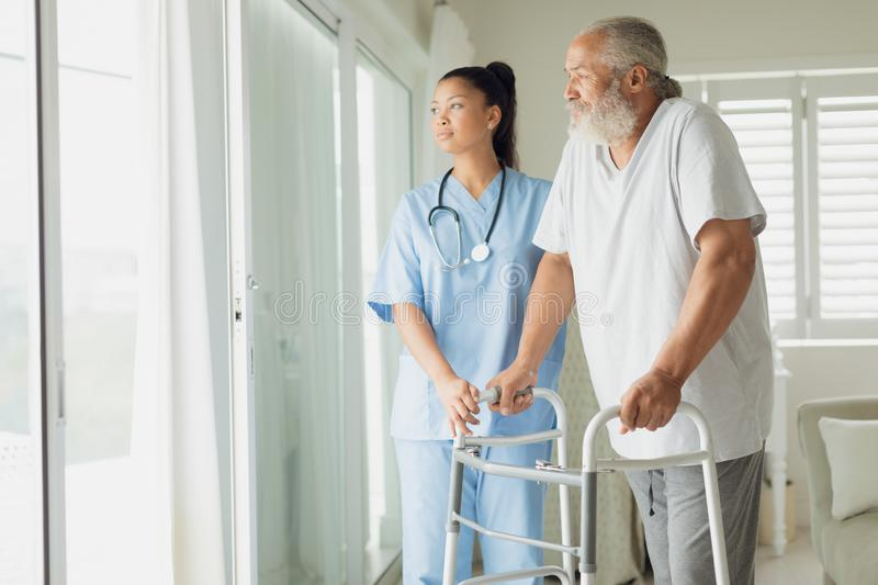 Healthcare worker with man using walking support. E view of healthcare worker with men using walking support indoor. Authentic Senior Retired Life Concept stock images