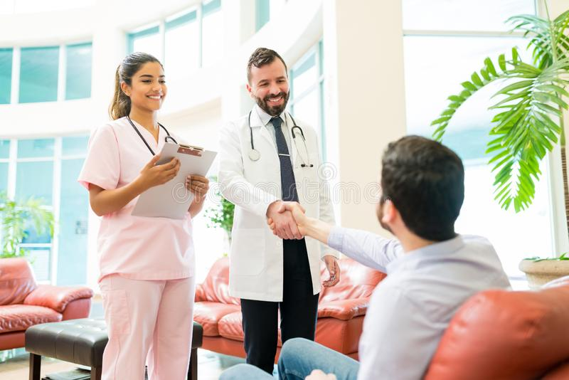 Healthcare Workers Greeting Man Waiting At Hospital royalty free stock photo