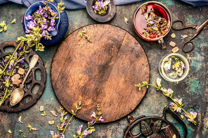 Healthful herbs tea setting around round wooden board on rustic background, top view. Frame stock photo