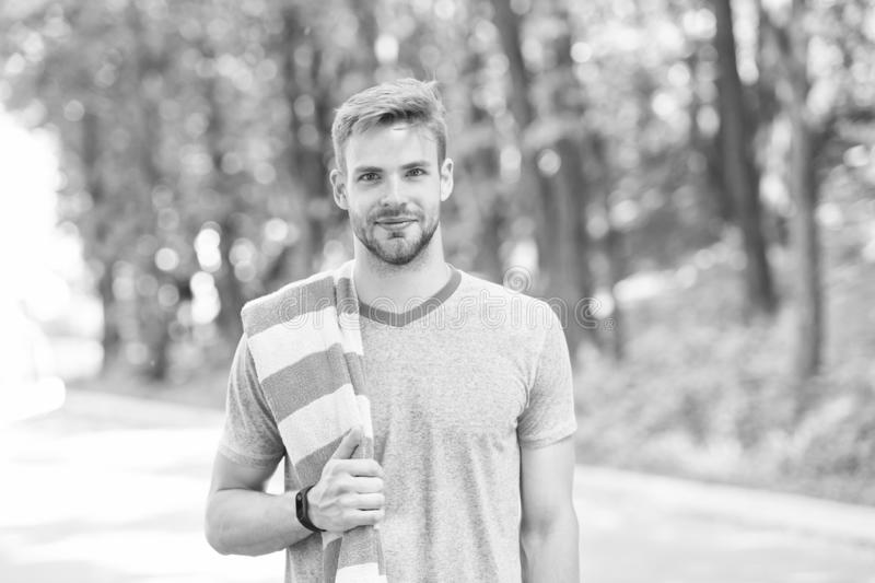 Healthy and active. Blond man. Handsome man wearing casual tshirt with towel on natural landscape. Man with unshaved royalty free stock image