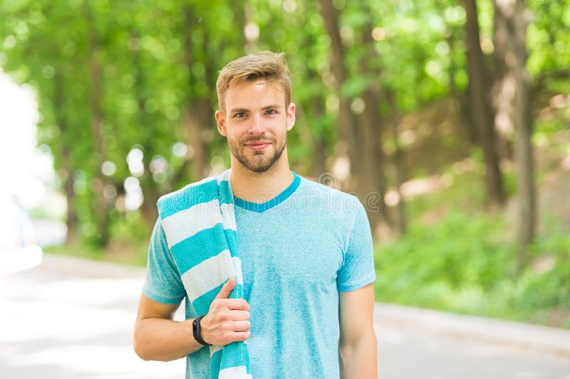 Healthy and active. Blond man. Handsome man wearing casual tshirt with towel on natural landscape. Man with unshaved. Face hair and stylish haircut. Caucasian royalty free stock photos
