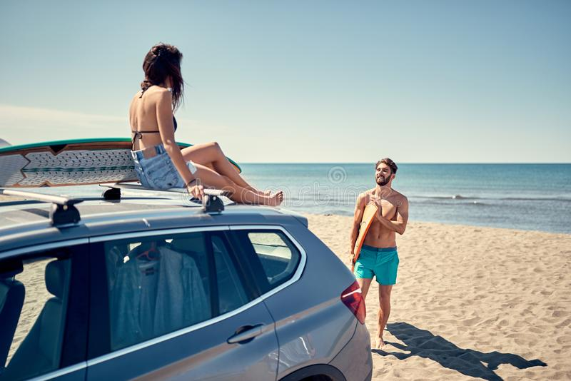 Healthy Active Lifestyle. Surfing. Summer Vacation. Extreme Sport. surfer girl sitting on the car and getting ready for surfing. royalty free stock photo
