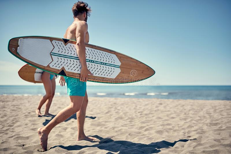 Healthy Active Lifestyle. Surfing. Summer Vacation. Extreme Sport. Young surfer man walking with board on the sandy beach. . Water sports. Healthy Active stock images