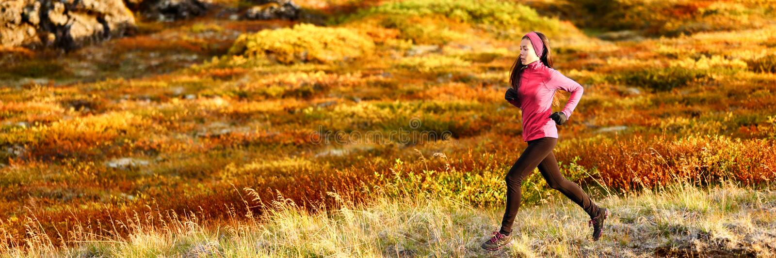 Healthy active lifestyle trail running athlete woman training outdoors doing cardio exercise in autumn foliage background. Panoramic banner royalty free stock photo