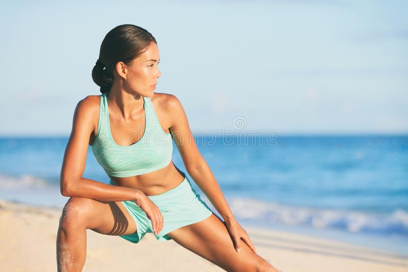Healthy active lifestyle woman stretching legs before running on beach run. Fitness workout morning routine in summer outdoors. Asian beauty girl runner on stock photos