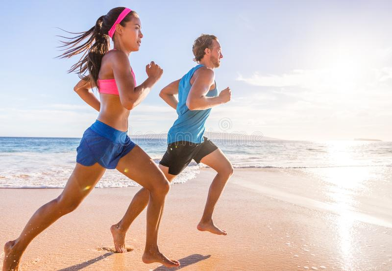 Healthy active runners couple running on beach working out cardio together. Fitness sports lifestyle royalty free stock images