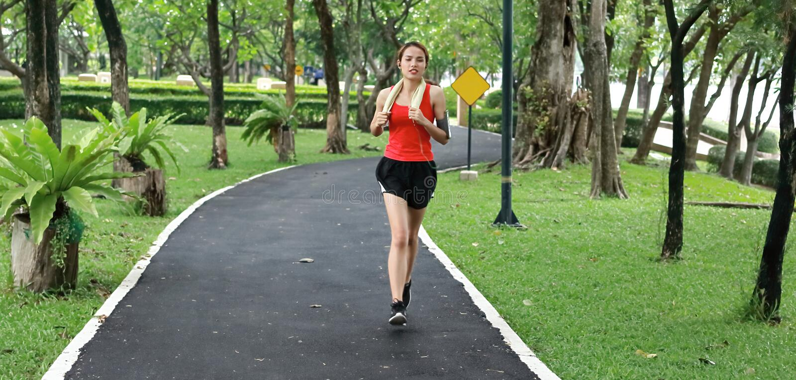 Healthy Asian fitness runner woman listening music and running workout in natural park stock photo