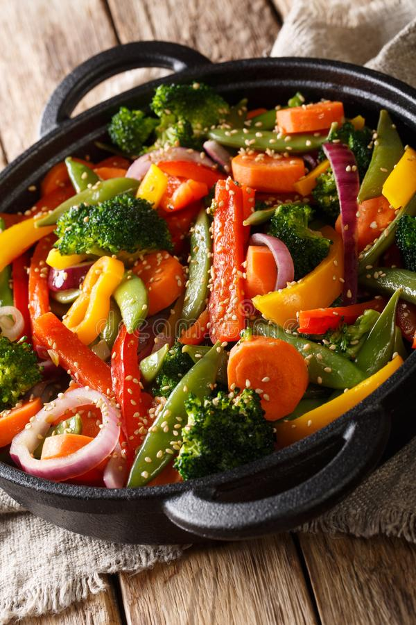 Healthy Asian food stir fry of vegetables with sesame close-up in a bowl, vertical royalty free stock image
