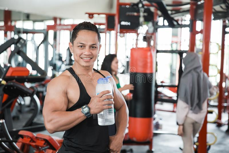 Healthy asian muscular man with drink stock image