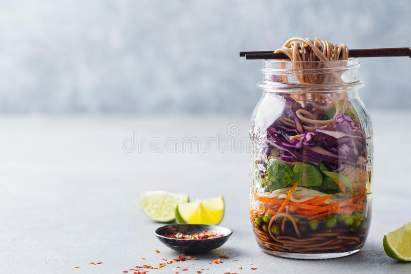 Healthy asian salad with noodles, vegetables, chicken and tofu in glass jars. Grey background. Copy space. royalty free stock photos