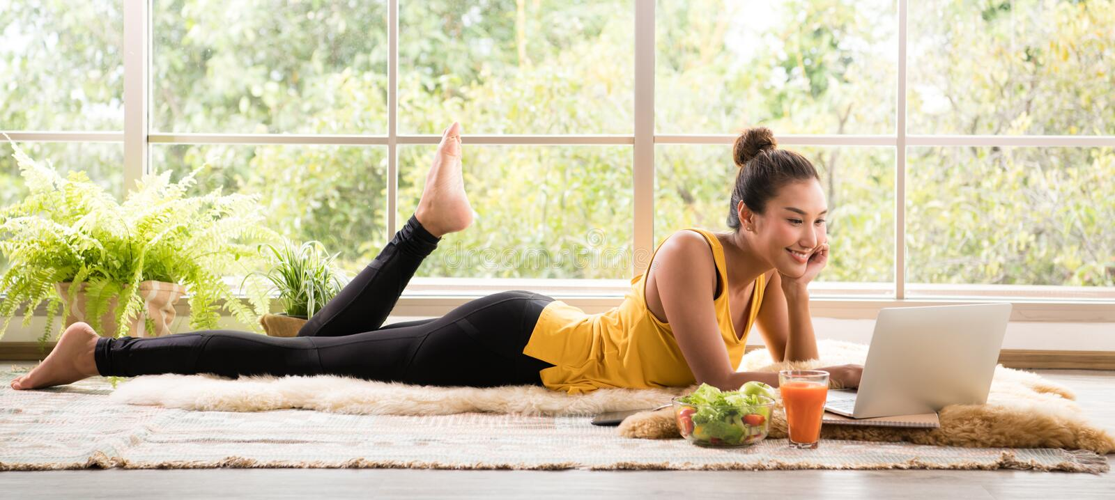Healthy Asian woman lying on the floor eating salad and looking at laptop computer royalty free stock image